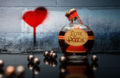 在一个瓶的媚药有浪花心脏的在背景中 免版税库存照片