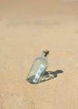 100在一个瓶的欧元在沙子 免版税库存照片