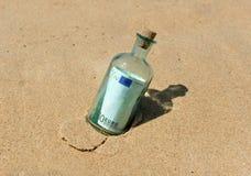100在一个瓶的欧元在沙子 库存照片