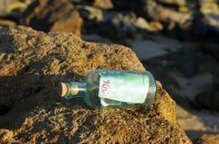 100在一个瓶的欧元在海滩的岩石 库存照片