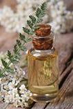在一个瓶的欧蓍草油有花垂直宏指令的 免版税库存图片