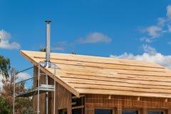 在一个生态家的大厦的不锈钢烟囱 节能木房子 村庄的建筑在fo附近的 免版税库存图片