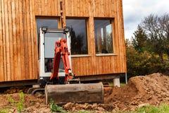 在一个生态房子的建造场所工作 挖掘机调整地形 一位小挖掘者在庭院里 免版税库存图片