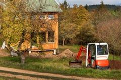 在一个生态房子的建造场所工作 挖掘机调整地形 一位小挖掘者在庭院里 库存照片