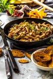 在一个生铁平底锅的油煎的黄蘑菇蘑菇在一张土气黑木桌上 免版税库存图片