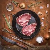在一个生铁煎锅的新鲜的未加工的猪肉牛排有肉叉子肉葱大蒜草本和香料的一把刀子的 木土气bac 库存图片