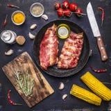 在一个生铁长柄浅锅的未加工的羊羔肋骨,有肉的一把刀子的、香料和草本和玉米木土气背景顶视图 免版税图库摄影