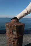 在一个生锈的系船柱的手 库存图片