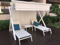 在一个甲板的白色海滩sunlounger在水池附近 与白色盖子的太阳床 免版税库存照片
