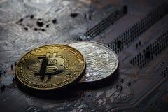 在一个电子计算机板的黑暗的背景的两枚硬币bitcoin 图库摄影