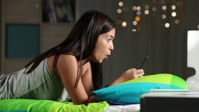 在一个电话的惊奇的青少年观看的媒介在床上 股票视频