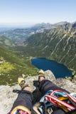 在一个登山人的脚的上升的鞋子在休息期间的在上升以后的上面 从Mnich的看法到湖Morskie Oko和surroundi 免版税库存照片