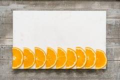 在一个白板堆积的橙色切片,刀子 免版税库存图片