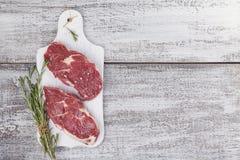 在一个白色切板的未加工的新鲜的牛排 免版税库存图片