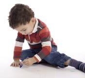 在一个白色地板上的小男孩图画 免版税库存图片