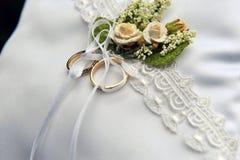 在一个白色坐垫,玫瑰色装饰的婚戒 免版税库存图片