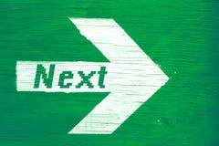 在一个白色定向箭头写的`下`文本绘在绿色木牌背景 免版税库存图片