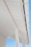在一个白色家的新的雨天沟反对蓝天 库存照片