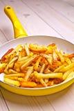 在一个白色平底锅的油煎的土豆 库存图片