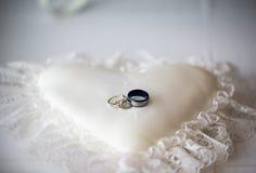 在一个白色心形的枕头的结婚戒指 库存照片