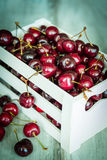 在一个白色木条板箱的樱桃在木背景 免版税图库摄影