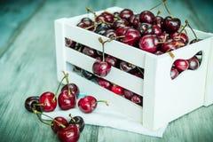 在一个白色木条板箱的樱桃在木背景 免版税库存图片