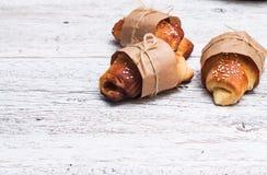 在一个白色木背景特写镜头包裹的三个小圆面包 免版税库存照片