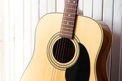 在一个白色木背景特写镜头的声学吉他 免版税库存图片