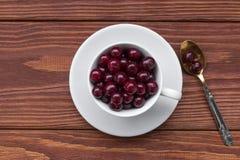 在一个白色杯子和一个茶匙的甜樱桃在一张木桌,选择的焦点,顶视图上 免版税图库摄影
