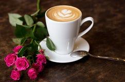 在一个白色杯子的一杯新鲜的早晨热奶咖啡有泡沫,在一张木桌上的立场的心脏的,在它附近说谎玫瑰 库存照片