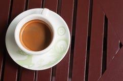 在一个白色杯子的咖啡在木背景 免版税库存图片