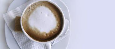 在一个白色杯子的咖啡热奶咖啡在一个白色餐巾和茶碟 特写镜头 安置文本 在视图之上 图库摄影