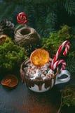 在一个白色杯子的圣诞节热巧克力用蛋白软糖、焦糖的桔子和棒棒糖在黑暗的背景,选择聚焦 图库摄影