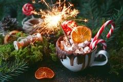 在一个白色杯子的圣诞节热巧克力用蛋白软糖、焦糖的桔子和棒棒糖有闪烁发光物的在黑暗的背景, Sel 免版税库存图片