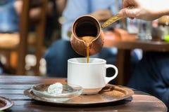 在一个白色杯子的妇女倾吐的希腊咖啡 库存图片