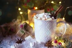 在一个白色杯子的热巧克力用蛋白软糖和圣诞节礼物在明亮的轻的背景 库存照片