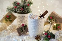 在一个白色杯子的热巧克力用蛋白软糖和圣诞节礼物 免版税库存图片