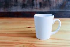 在一个白色杯子的热的咖啡在木桌上 免版税图库摄影