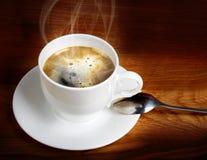 在一个白色杯子的热的新鲜的咖啡有匙子的 免版税库存图片