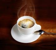 在一个白色杯子的热的新鲜的咖啡有在木桌上的匙子的 免版税库存图片
