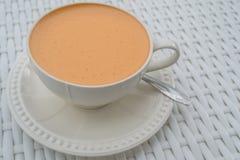在一个白色杯子的热的牛奶茶 免版税库存图片