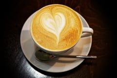 在一个白色杯子的特写镜头热奶咖啡在黑桌上 免版税库存图片