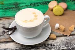 在一个白色杯子的香草热奶咖啡用糖和蛋白杏仁饼干在木桌上 库存图片