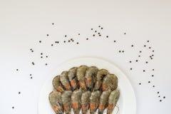 在一个白色板材和黑胡椒豌豆的新鲜的未煮过的国王大虾在白色背景 纤巧,鲜美和健康海鲜, 免版税图库摄影