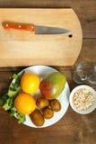 在一个白色板材谎言芒果猕猴桃桔子的一张木桌上 在背景中一个木切板和刀子 垂直的图象 图库摄影