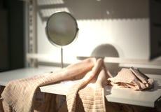 在一个白色架子的毛巾在卫生间和一个圆的镜子里 免版税库存图片