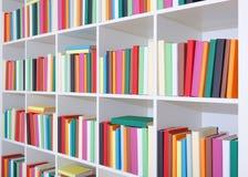 在一个白色架子,堆的书五颜六色的书 免版税库存图片