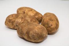 在一个白色柜台的四个土豆 库存图片