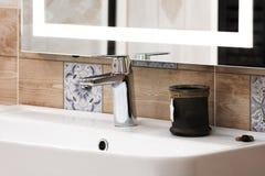 在一个白色水槽的豪华现代样式龙头搅拌器在一个美丽的卫生间里 库存图片