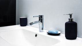 在一个白色水槽的豪华现代样式龙头搅拌器在有桃红色玻璃辅助部件的一个美丽的灰色和白色卫生间里 库存图片